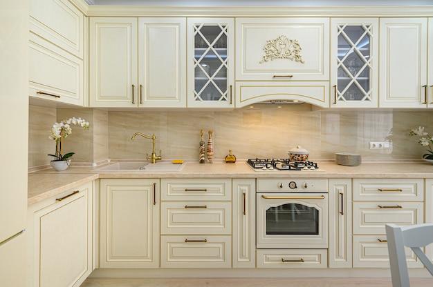 Интерьер современной классической кухни бежевого цвета выполнен в стиле прованс Premium Фотографии