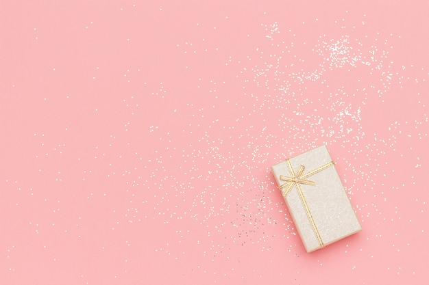 Beige gift box with bow in corner on pink Premium Photo