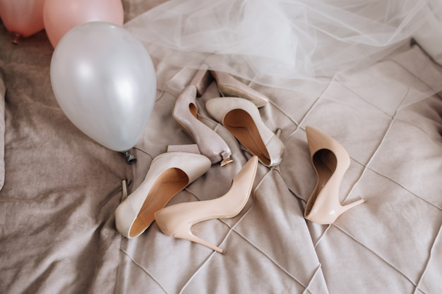 Beige shoes are lying on the blanket near veil and balloons Free Photo