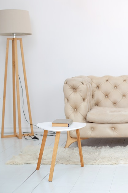 Бежевый диван с журнальным столиком и лампой на полу в интерьере уютной гостиной. диван на белой стене. интерьер гостиной в скандинавском стиле. лобби. интерьер комнаты в загородном доме. Premium Фотографии
