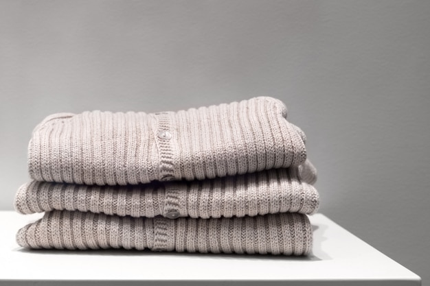 Beige sweaters made from natural fabrics are folded on the table Premium Photo