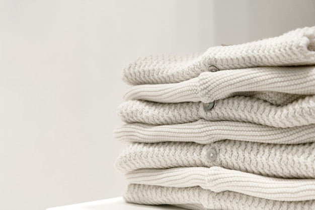 Beige sweaters made from natural fabrics are folded on the table. Premium Photo