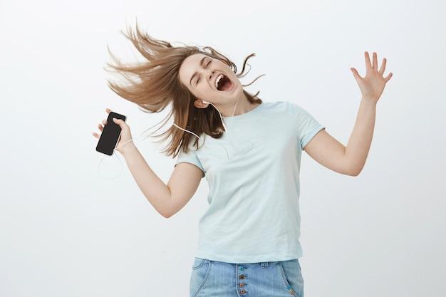 Essere selvaggio e libero mentre si ascolta una bella canzone. donna felice allegra che salta e balla con capelli castani mossi, occhi chiusi che canta lungo la musica d'ascolto della canzone preferita in cuffie che tengono smartphone Foto Gratuite