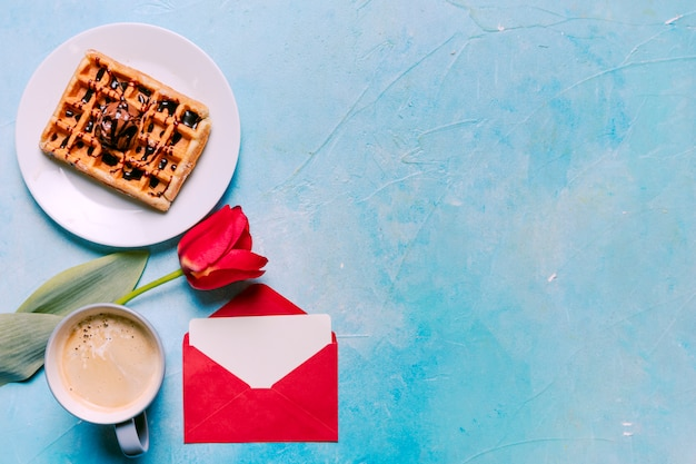 Belgian waffle on plate with red tulip Free Photo