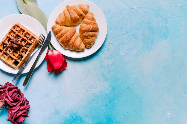 Belgian waffle with croissants and flowers Free Photo