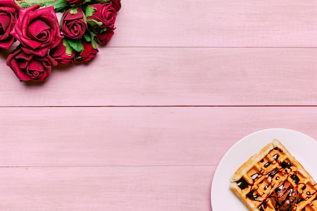 Belgian waffle with red roses bouquet on table Free Photo