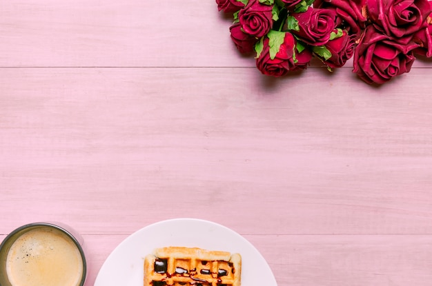 Belgian waffle with roses bouquet and coffee Free Photo