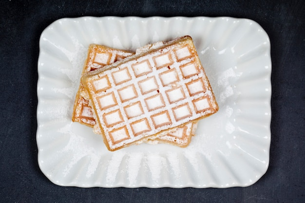 Belgium waffers with sugar powder on ceramic plateon black board background. Premium Photo