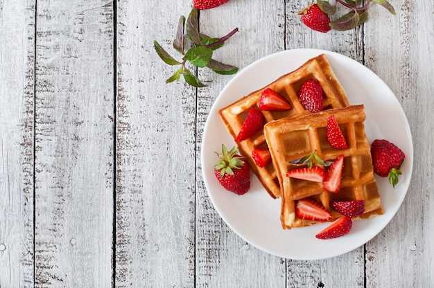 Бельгийские вафли с клубникой и мятой на белой тарелке Бесплатные Фотографии