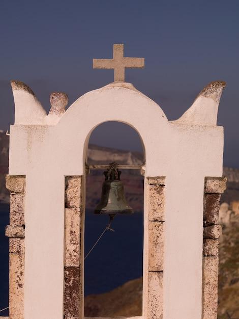 Bell and crucifix on church in santorini greece Premium Photo