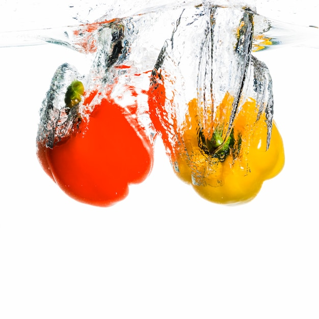 Bell pepper falling into water forming splash against white background Free Photo