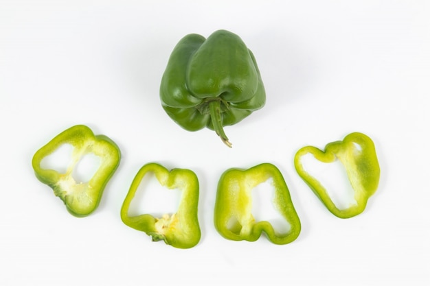 Peperone dolce verde fresco ed affettato sul pavimento bianco Foto Gratuite