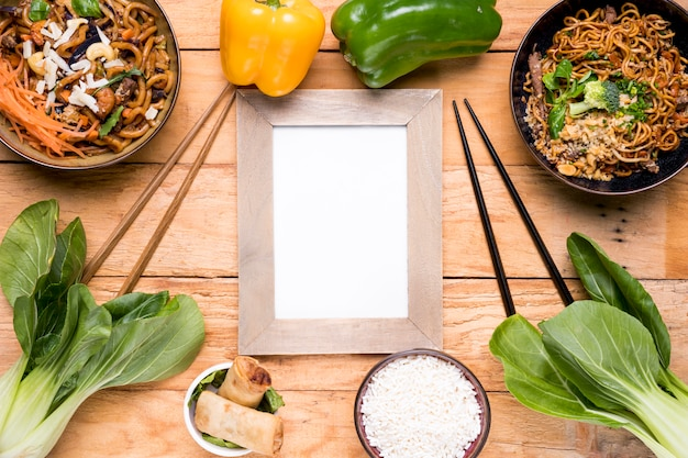 Bell peppers; bokchoy; chopping stick; spring rolls; rice and udon noodles bowl on wooden desk Free Photo