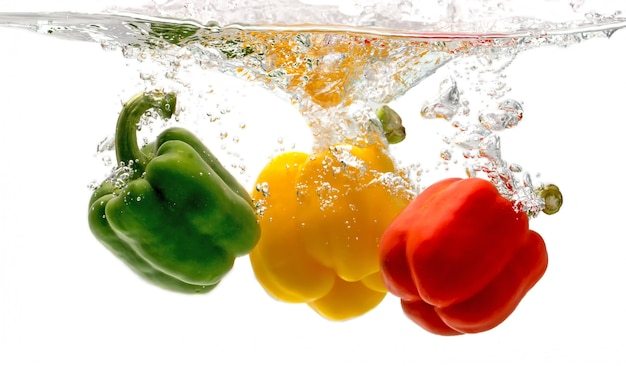 Bell peppers falling into the water looks so fresh. Premium Photo