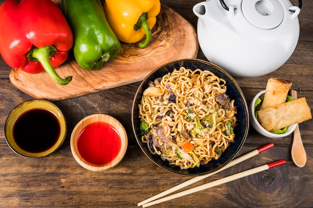 Bell peppers; udon noodles; sauces and spring rolls on white desk Free Photo