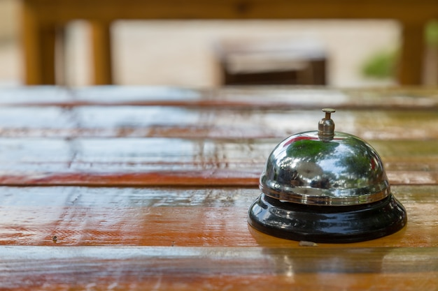 Bell on the wood table in restaurant with nature background Premium Photo