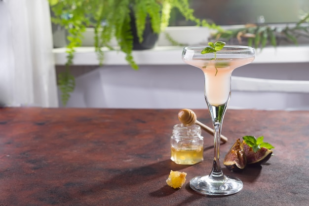 Bellini cocktail with peach and figs, honey on brown background over windows Premium Photo