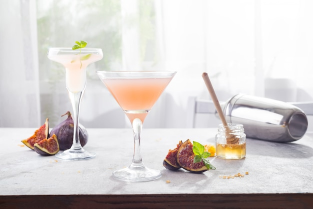 Bellini cocktail with peach and figs, honey on light background over windows, copy space Premium Photo