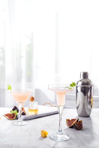 Bellini cocktail with peach and figs, honey on light background over windows Premium Photo