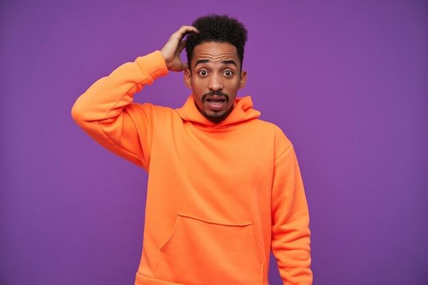 困惑した若いひげを生やした暗い肌のブルネットの男は、紫色に立って、広い目と口を開いて頭に手を上げた 無料写真