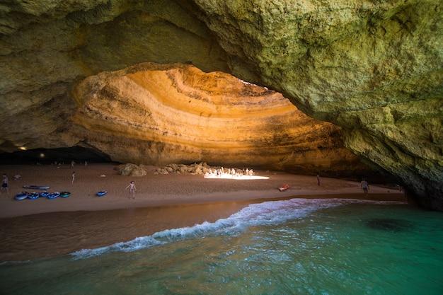 Прогулка на лодке по пещере бенагил в альгар-де-бенагил, пещере, включенной в 10 лучших пещер мира. побережье алгарве около лагоа, португалия. туристы посещают популярную достопримечательность Бесплатные Фотографии