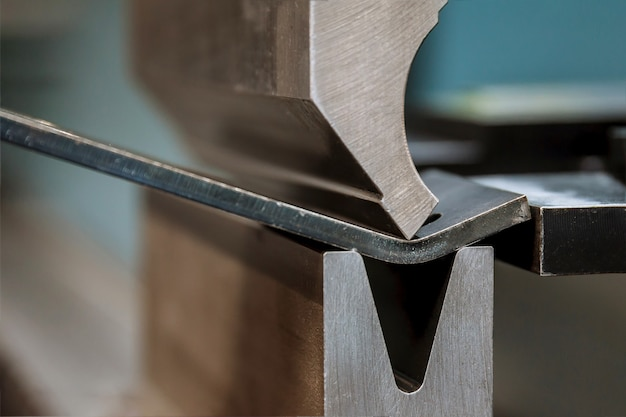 Гибка листового металла на гидравлическом станке на заводе. крупный план. Premium Фотографии