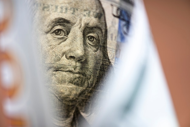 Benjamin franklin face on us dollar banknote. us dollar is main and popular currency of exchange in the world. investment and saving concept. Premium Photo