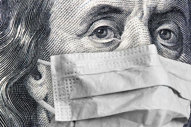 ベンジャミンフランクリンの肖像画医療マスクで100ドル紙幣のクローズアップ Premium写真