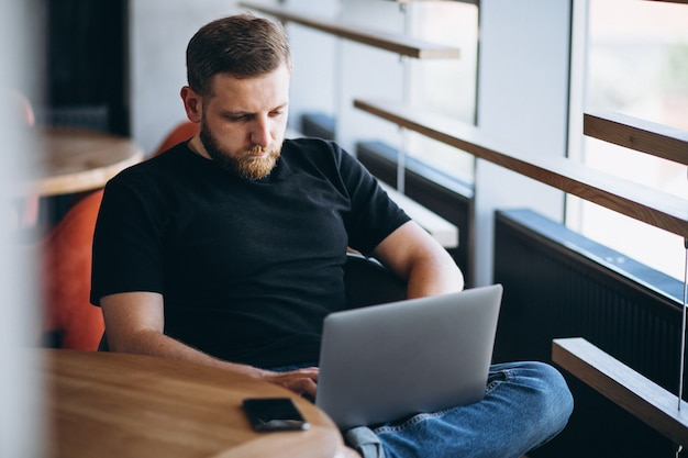Beraded man working on laptop in a cafe Free Photo