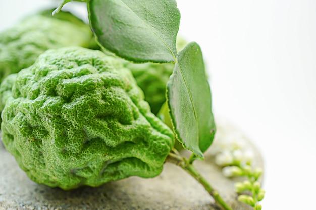 Bergamot fresh fruit on wooden background with yellow flower : natural herb Premium Photo