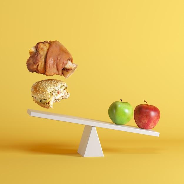黄色の背景に反対側の端にフローティングbergersと豚足とシーソーを傾けているりんご。 Premium写真