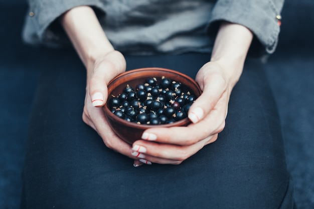 Berries of black currant in plates in female hands. vitamins and healthy eating concept Premium Photo
