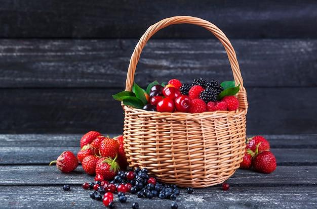 Berries mix in basket on dark wooden Premium Photo