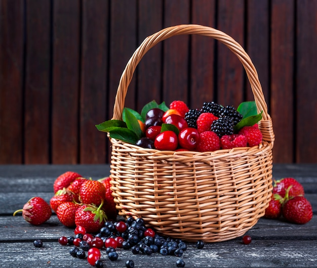 Berries mix in basket on rustic wooden background Premium Photo