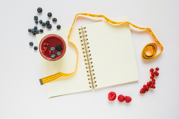 Berries; smoothie glass; measuring tape and spiral notebook on white background Free Photo