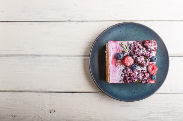 Berry cake with milk cream and blueberry jam on blue ceramic plate. top view. Premium Photo