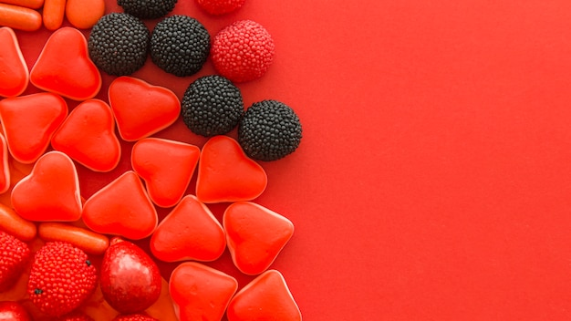 Berry fruit and heart shape candies on red background Free Photo