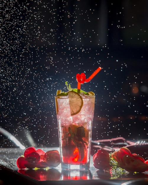 Berry lemon cocktail with red pipe and ice cubes in black starry background. Free Photo