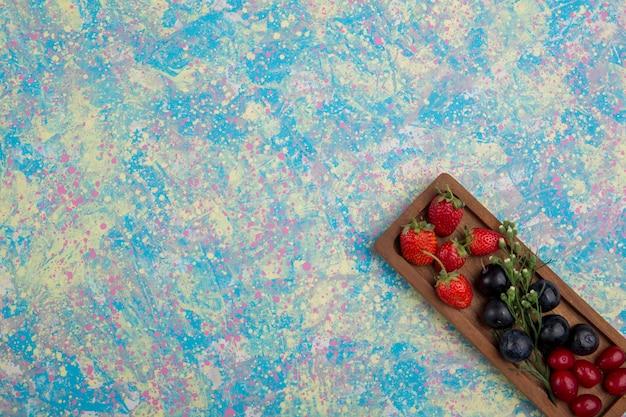 Ягодная смесь на деревянном блюде изолирована в углу Бесплатные Фотографии