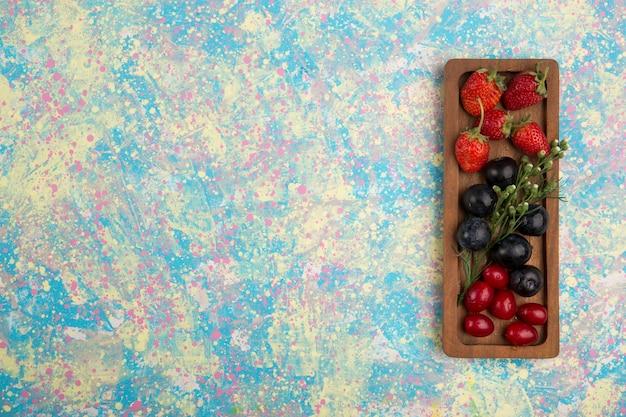 Ягодная смесь на деревянном блюде, изолированные на синем фоне Бесплатные Фотографии