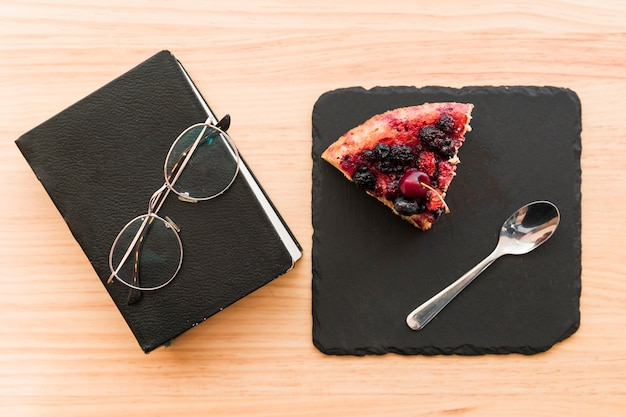 Berry pastry near diary and spectacles on wooden desk Free Photo