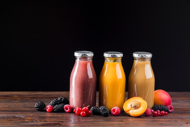 Berry and peach smoothies on wooden surface Free Photo