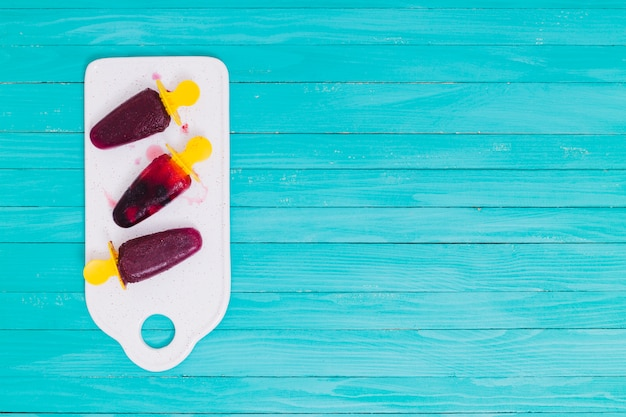 Berry popsicles on a white cutting board on a wooden surface Free Photo