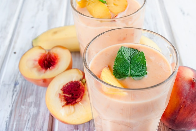 Berry smoothies of apricot, peach and banana  in glasses and ingredients on a wooden table Premium Photo
