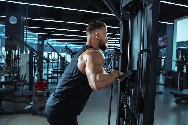 Scelta migliore. giovane atleta caucasico muscoloso allenamento in palestra, facendo esercizi di forza, praticando, lavorare sulla parte superiore del corpo con pesi e bilanciere. fitness, benessere, concetto di stile di vita sano. Foto Gratuite