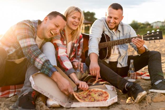 ビーチでピザを食べる親友 無料写真