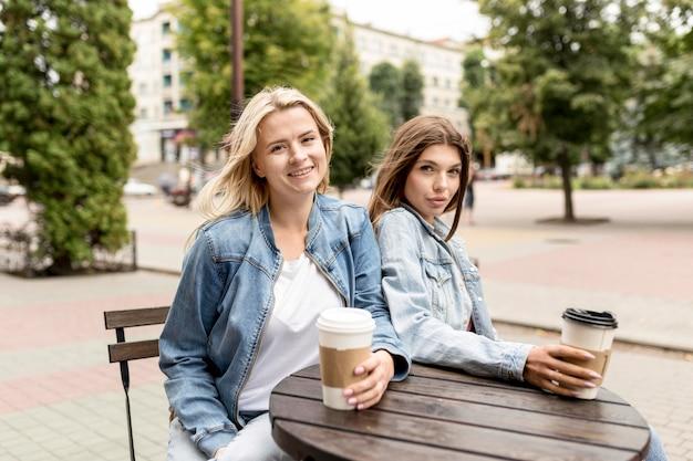 Migliori amici che si godono una tazza di caffè fuori Foto Gratuite