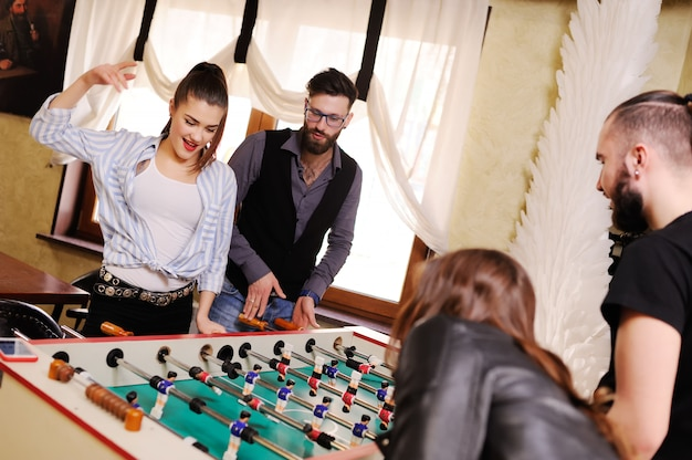 Best friends - guys and girls play table footbal Premium Photo