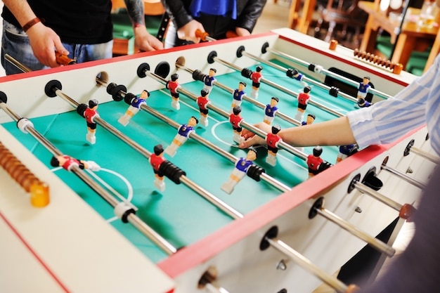 Best friends - guys and girls play table football. Premium Photo