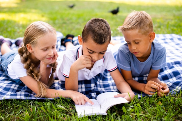 Best friends reading on a picnic blanket Free Photo